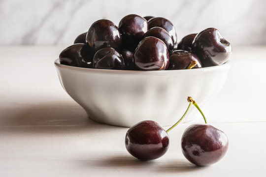 close of fresh organic summer ripe juicy cherry black cherries in a white porcelain bowl room for text  fileld frame