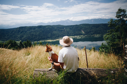 Young male hiker or adventurer tourist takes rest at scenic overlook at field on top of mountain together with pet dog basenji brown puppy. Healthy lifestyle and outdoor activities