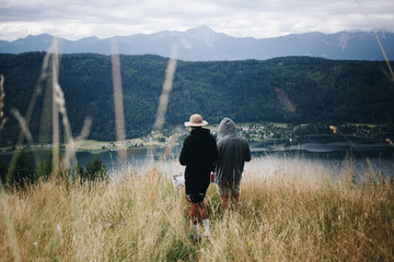 Two man in hiking or camping outdoor outfits stand in middle of alpine field, overlook valley with beautiful lake at bottom during summer vacation in national park