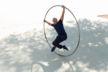 Cyr wheel acrobat stretching in a park outdoors