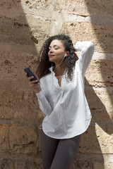 Beautiful woman under a beam of light listen music with headphones