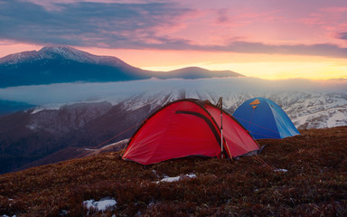 Tourist camping in autumn mountains. Two tents on nacbkground of sunrise