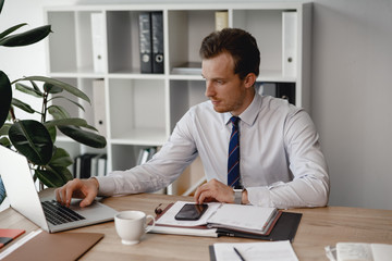 Man in shirt and tie using laptop while working