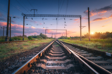 Railway station and beautiful sky at sunset. Summer rural industrial landscape with railroad, blue sky with colorful clouds and sunlight, green grass. Railway platform. Transportation. Heavy industry