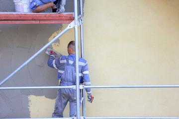 Tynkarze na rysztowaniu w trakcie nakładania tynku na ścianę budynku.