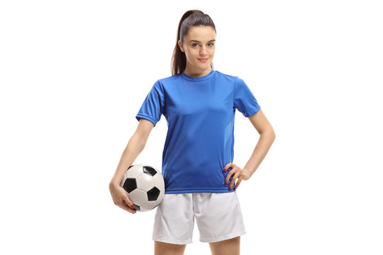 Female soccer player posing with a football