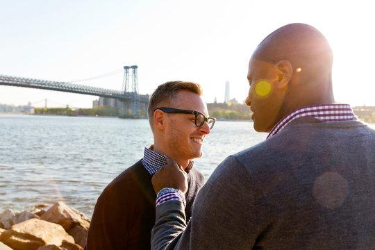 Two happy men standing on promenade with Brooklyn Bridge in background