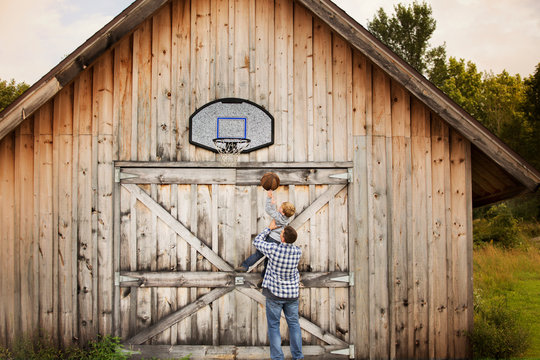 Father and son playing basketball in front of wooden barn