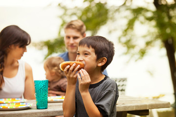 Family with kids (6-7, 12-17 months) eating at picnic table