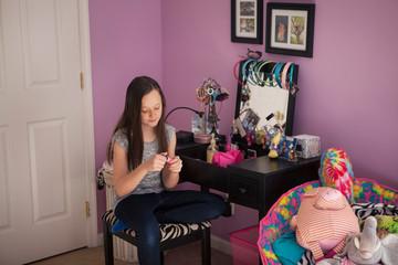Girl looking at nail polish at home