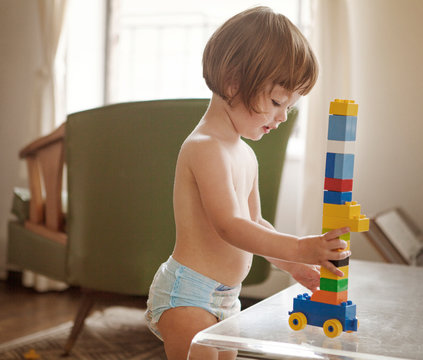 Shirtless girl playing with toy blocks at home