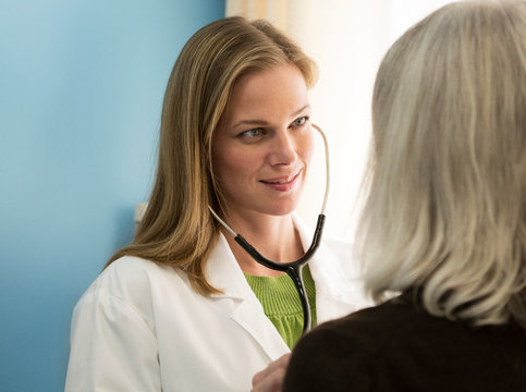 Female doctor listening to heartbeat of patient