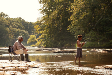 Grandfather looking at his grandson fishing in river Fototapete