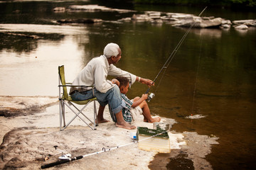 Boy and grandfather fishing in river