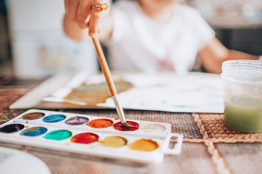 Beautiful blonde girl painting with paintbrush and water colors in the kitchen. Kid activities concept. Close up. Toned.