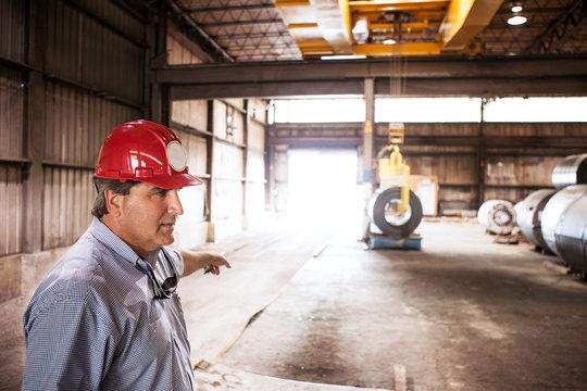 Man wearing hardhat pointing in warehouse