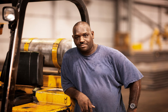 Portrait of worker standing next to forklift