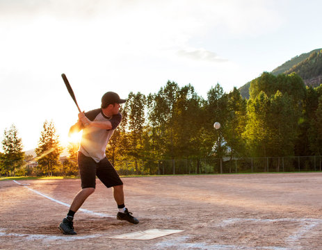 Softball player hitting ball in playing field