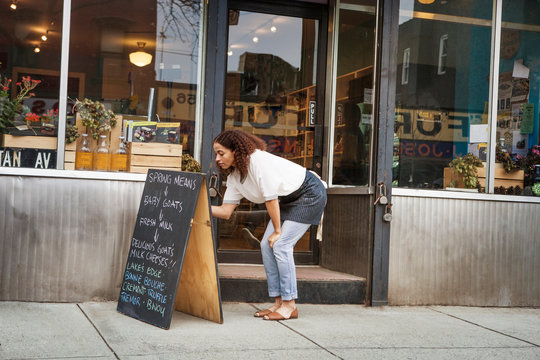 Small business owner writing on blackboard