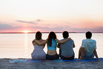 Young people watching sunset from beach