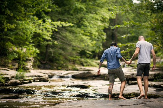Rear view of couple walking by stream in forest