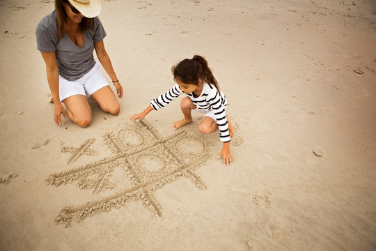Mather and daughter (6-7) playing tic-tac-toe on beach