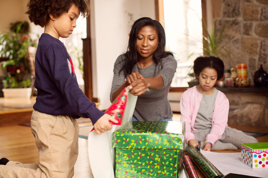 Children (6-7) helping woman with wrapping christmas presents