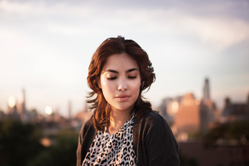 Portrait of young woman with skyline in background