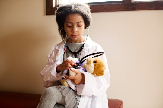 Girl (6-7) listening to teddy bear heart with stethoscope