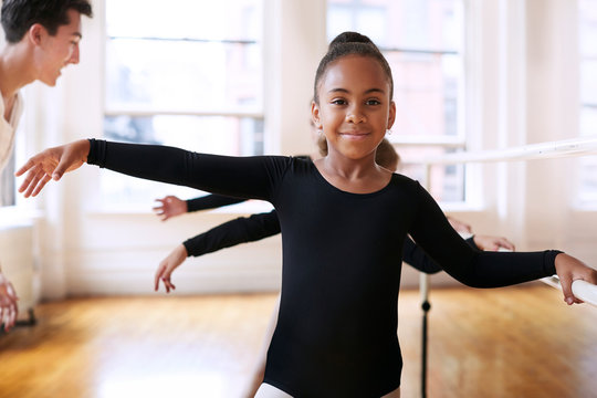 Portrait of girl practicing with ballet teacher