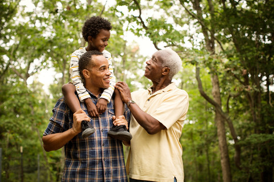 Smiling multigenerational family standing in forest