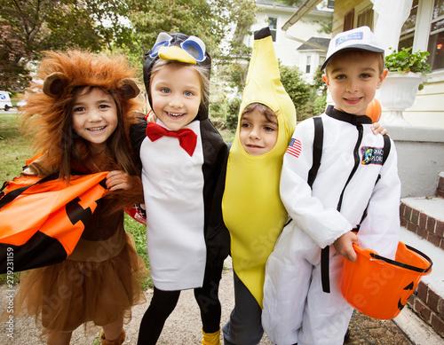 Portrait of smiling friends in Halloween costume standing outdoors