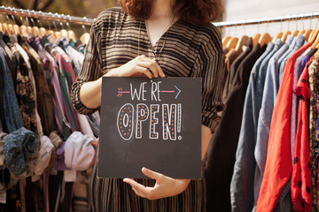 Mid section or woman holding open sign with clothes racks on background