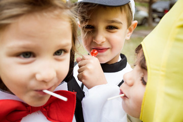 Close up of children in costumes eating lollipops