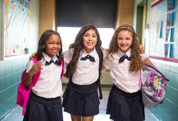 Portrait of three smiling schoolgirls (6-7, 8-9) standing in school corridor