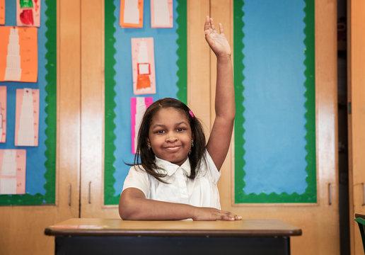 Portrait of school girl raising her hand in classroom