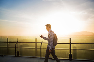 Man with mobile phone walking on terrace backlit image