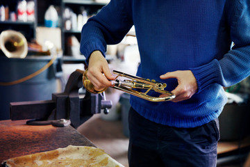 Mid-section of man holding trumpet