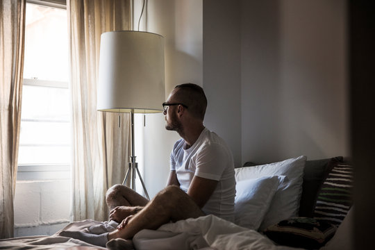Man sitting on bed and looking through window