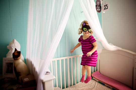 Girl wearing mask jumping on bed