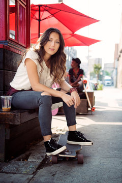 Young female sitting on street bench with skateboard build structure and red sunshades in background