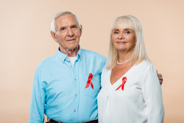 Obraz happy senior couple with red ribbons as hiv awareness isolated on beige - fototapety do salonu