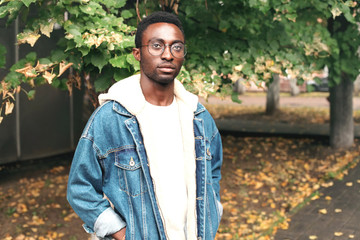Wall Mural - Fashion portrait african man wearing jeans jacket, eyeglasses in autumn park with leaves
