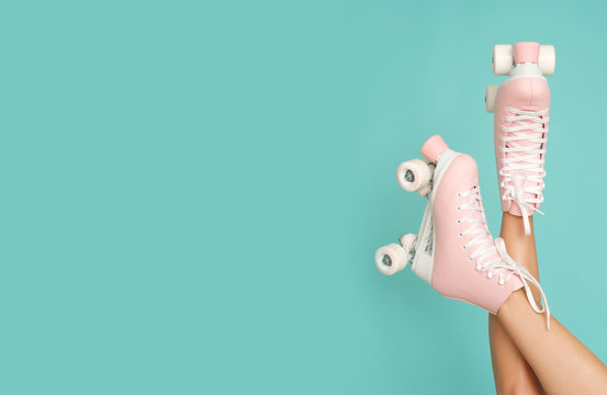 Legs up! Roller skates on slim leg isolated on the colorful background.
