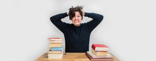 Mensch ist überfordert und hat Stress beim Lernen am Schreibtisch mit Büchern