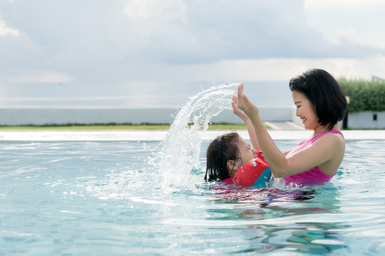 Happy Asian mother and daughter having fun in hotel swimming pool near sea enjoying summer vacation. Asian family concept.