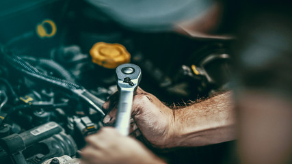 Fotobehang - Auto mechanic working on car engine in mechanics garage. Repair service.