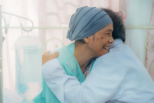 asian senior cancer patient during chemo therapy feel happy with smiling face and confident have hugging with doctor