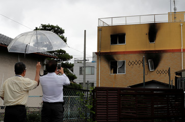 A man takes photos of the torched Kyoto Animation building after an arson attack in Kyoto