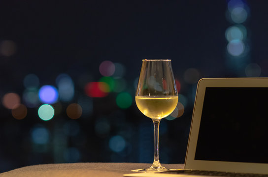 A glass with white wine puts on sofa with laptop computer with colorful bokeh light from city.